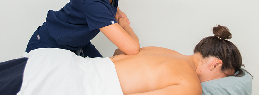 massage therapist performing massage on patients back