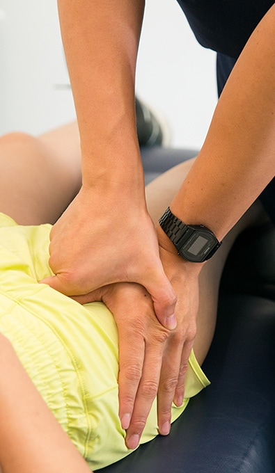 physiotherapist placing pressure on patients hip